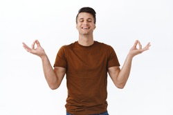 Portrait of relieved and happy, healthy young man smiling with calm and relaxed face, closed eyes, hold hands sideways in nirvana lotus pose, meditating and breathing freely, white background