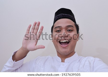 Portrait of religious Asian man in koko shirt or white muslim shirt and black cap taking picture of himself or selfie, saying hi and waving his hand. Isolated image over white background Imagine de stoc ©