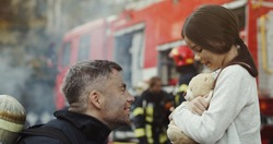 Portrait of rescued little asian girl with firefighter man standing near fire truck. Firefighter in fire fighting operation