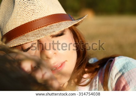 Portrait of resting young girl in a hat on field with hay bales in sunny summer day