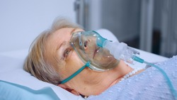 Portrait of retired senior woman breathing slowly with oxygen mask during coronavirus covid-19 outbreak. Old sick lady lying in hospital bed, getting treatment for deadly infection