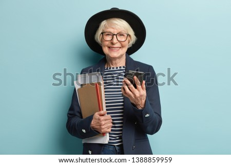 Portrait of retired teacher with grey hair, wrinkled skin, carries papers and notebook, checks notification on modern smartphone device, wears elegant apparel with stylish headgear, spectacles
