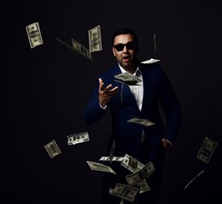 Portrait of rich successful businessman in blue jacket, white shirt and sunglasses standing throwing dollars cash at camera, wasting money, ready to buy over dark background