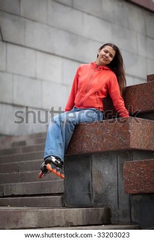 Portrait of rollerskating girl on granite stairs - shallow DOF - stock photo