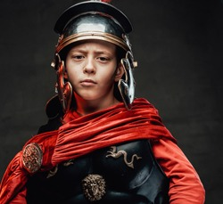 Portrait of roman military kid in dark armour with red cloak which poses in dark background looking at camera.