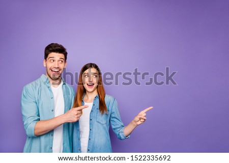 Portrait of romantic excited couple of business people freelancer scream wow look at copyspace point index finger ads tips wear denim jeans clothes isolated over violet purple color background