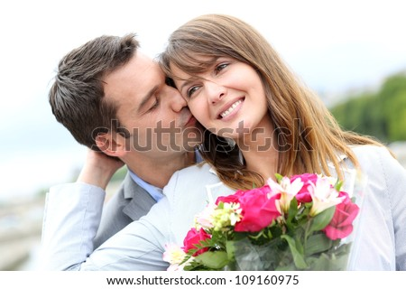 Portrait of romantic man giving flowers to woman