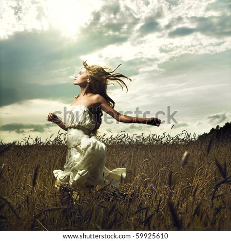 Portrait of romantic woman running across field - stock photo