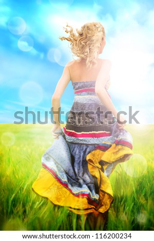 Portrait of romantic woman running across field wearing bright elegant dress