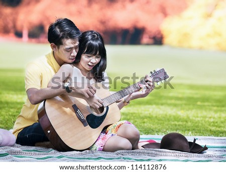 Portrait of romantic young couple playing a guitar in the park on autumn day - stock photo