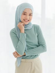 Portrait of 30s beautiful Muslim girl wearing hijab traditional religious cloth use hand touch her chin and looking to camera with a lovely smile on white background.