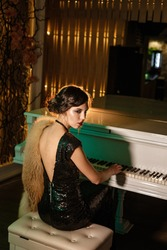 Portrait of 20s style festive beauty in a restaurant. Young beautiful woman in art-deco style, in black dress in a luxurious interere Chicago 20s, the era of gangsters. Singer  at the white piano