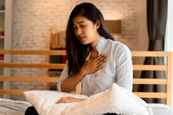 Portrait of 20s young Asian woman having difficulty breathing in bedroom at night. Shortness of breath, asthma, difficult to breathe problems. Corona Virus symptoms.
