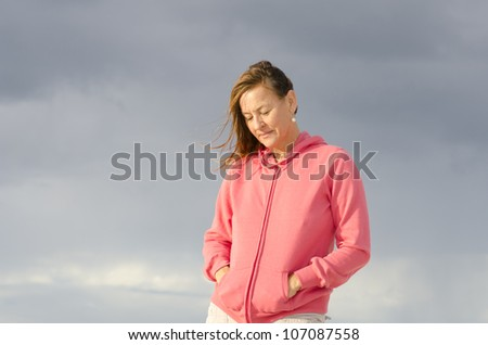 Portrait of sad and depressed looking mature woman in pink sweater, at beach, isolated with storm clouds as background and copy space.
