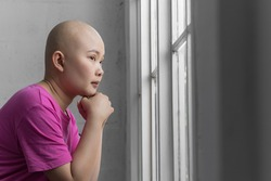 Portrait of sad Asian woman cancer patient after suffering serious hair loss due to chemotherapy