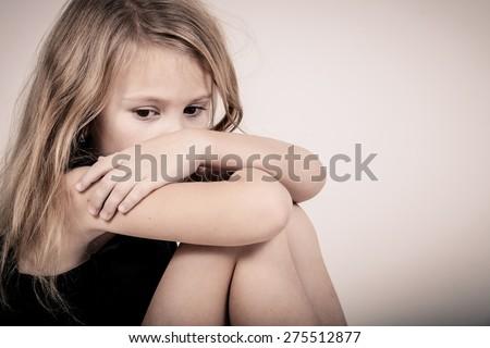 Portrait of sad blond little girl sitting near white wall