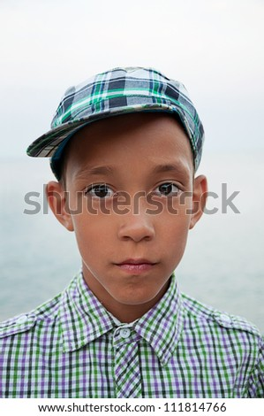 portrait of sad boy with brown eyes in cap and shirt looking at camera