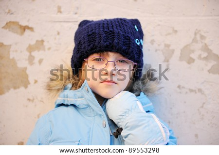 Portrait of sad child girl wearing warm winter clothes against the wall