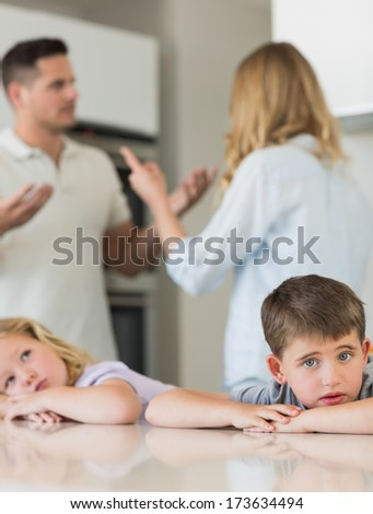 Portrait of sad children leaning on table while parents arguing in background at kitchen