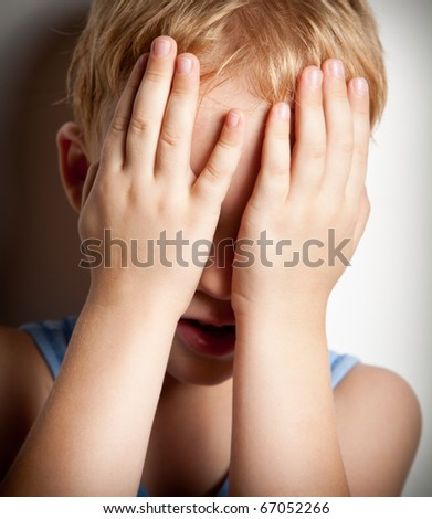 Portrait of sad crying little boy covers his face with hands