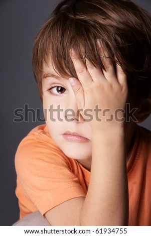 Portrait of sad cute little boy closed one eye with his hand, studio shot