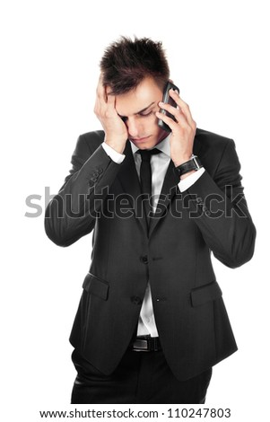 Portrait of sad, depressed young businessman talking on phone