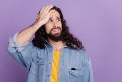 Portrait of sad guy hand head look empty space on violet background