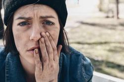 Portrait of sad homeless woman outdoors
