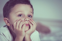 Portrait of sad little boy lying on bed at the day time. Concept of sad childhood.
