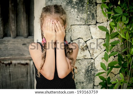 Portrait of sad little girl standing near stone wall at the day time