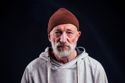 portrait of sad old senior male tramp wearing warm brown hat and leaky gloves,holding metal canned bank jar for money alms in studio black background.
