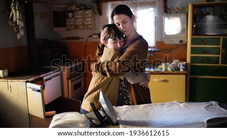 Portrait of sad poor mature mother hugging small daughter indoors at home, poverty concept. Foto stock ©