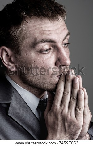 Portrait of sad praying businessman looking for solutions