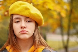 Portrait of sad teen girl in yellow beret. Autumn melancholy and depression concept.