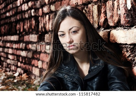 Portrait of sad teenage girl against old brick wall background.