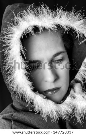 Portrait of sad woman in black cape with feather black and white
