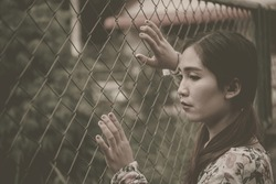 Portrait of sad woman,  she touches fence. vintage style,dark tone, film tone, pastel,film tone