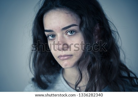 Portrait of sad young teen girl feeling unhappy, miserable and melancholy suffering from depression. In facial expressions, negative emotions and emotional pain in youth. isolated on moody background.