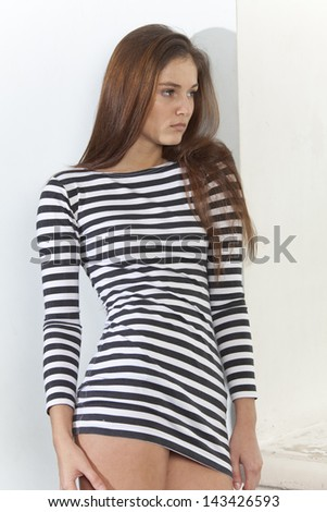 Portrait of sad young woman in short striped shirt