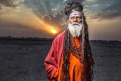 Portrait of sadhu standing with sunrise behind him, Varanasi, India.