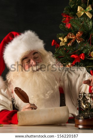 Portrait of Santa Claus answering Christmas letters using vintage tools - paper roll, feather pen, ink, wooden retro phone