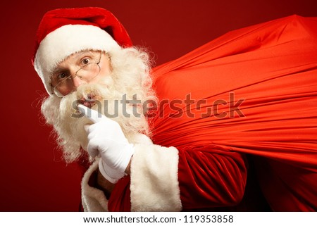 Portrait of Santa Claus carrying huge red sack and showing gesture of silence