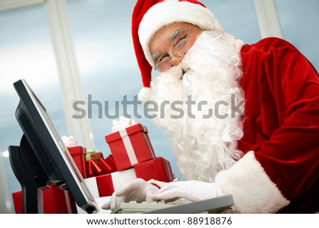 Portrait of Santa Claus in front of computer monitor looking at camera