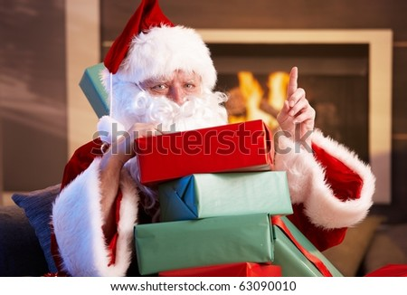 Portrait of Santa Claus sitting by fireplace holding a pile of Christmas presents.?