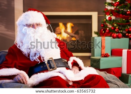 Portrait of Santa Claus sitting by fireplace with Christmas presents all around, looking at camera.?