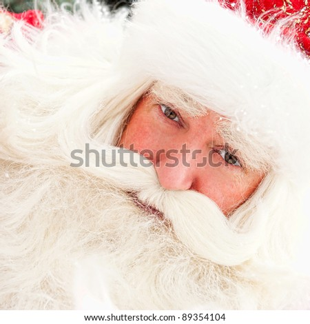 Portrait of Santa Claus standing outdoors. Snow falls. Natural light
