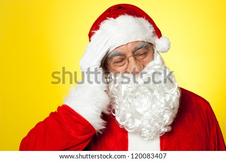 Portrait of Santa Claus suffering from headache. All on yellow background