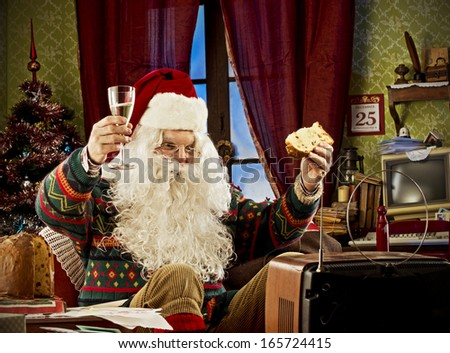 Portrait of Santa Claus watching tv celebrating with a glass of champagne and panettone