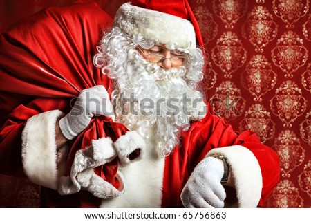 Portrait of Santa Claus with a bag of presents and looking at his watch. Christmas.