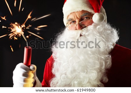 Portrait of Santa with a sparkler isolated on black